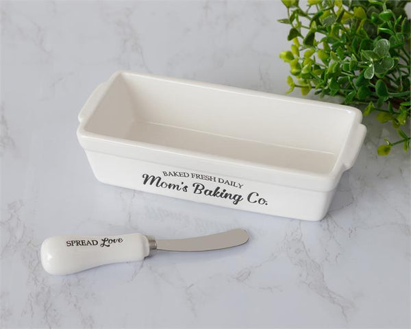White rectangle shaped butter dish is shown with a ceramic handled server as well. The side of the white dish has black imprinted words that say Mom's Baking Co., baked fresh daily. The spreader says spread love.