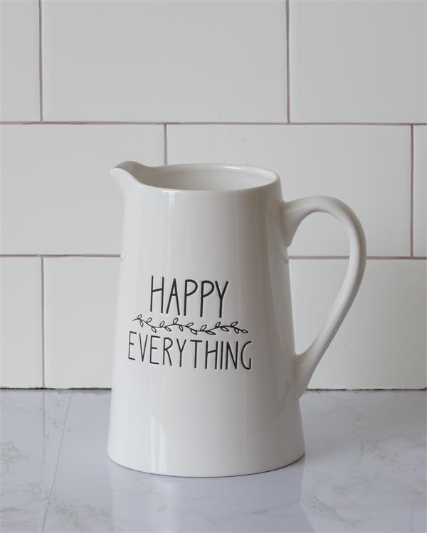 A white ceramic pitcher with the words Happy Everything on the side in black. There is small black florals between the words. It is empty demonstrating that is could be used a juice or water pitcher.