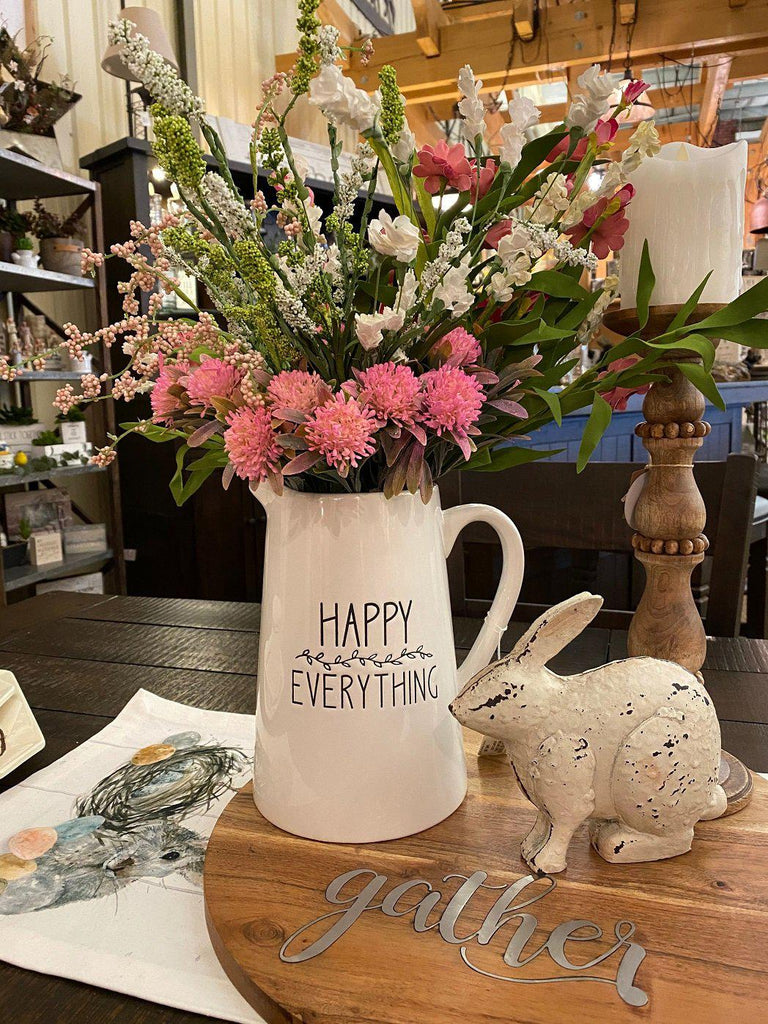 A white ceramic pitcher with the words Happy Everything on the side in black. There is small black florals between the words. It is filled with seasonal coloured florals.