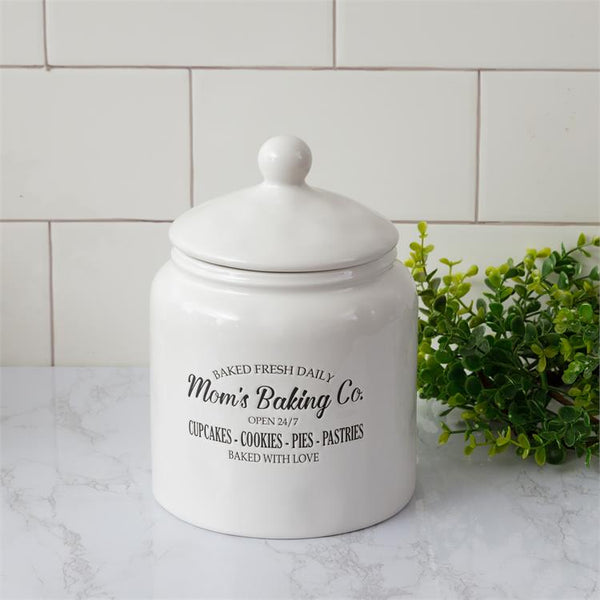 White ceramic cookie jar with lid is pictured. This farmhouse style jar has Mom's Baking Co. open 24/7, baked fresh daily imprinted on the side. It has a white removable lid.