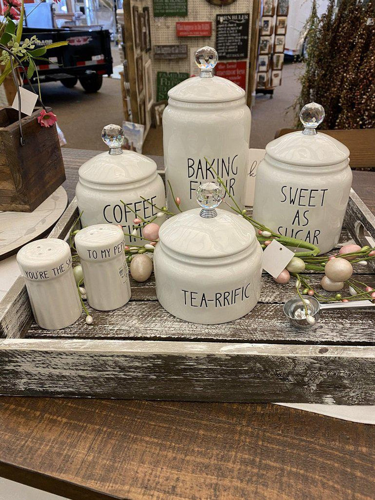 Grouping of white canisters in a decorative Tray. There is four white ceramic canisters , one for coffee, one for flour, one for sugar and one for tea. All have glass knobs. There is also a white set of salt and pepper shakers..