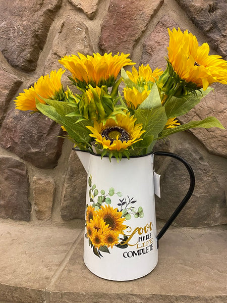 A white enamel pitcher is filled with beautiful sunflowers. The pitcher is white enamel, and has a black slim handle, and black painted trim around the top and spout. The picture on the side is of a bouquet of sunflowers and says Love makes life Complete.