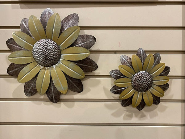 "Two galvanized metal daisy-styled flowers. The centres of the flower are hammered metail and then two layers of petals, the top layer is a muted yellow and the second layer that peeks out underneath is gray metal. The large on is 12"" diameter and the small one is 8"" in diameter."