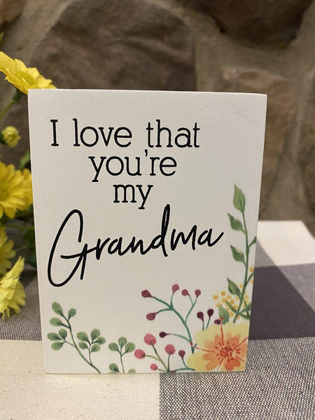 "This is a 4"" high wooden box sign that is painted white. It is one inch deep and with black lettering it says I love that you're my Grandma. In the bottom right hand corner there is painted yellow flowers and green leaves."