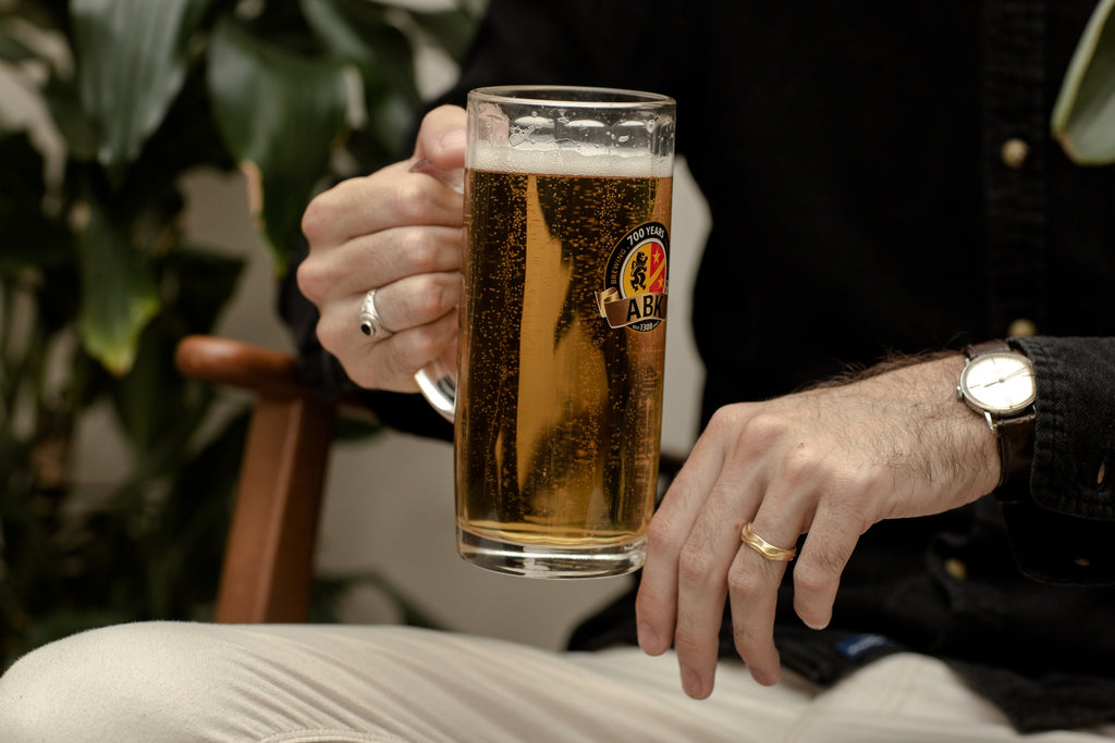 Young man drinks ABK Hell Beer at home