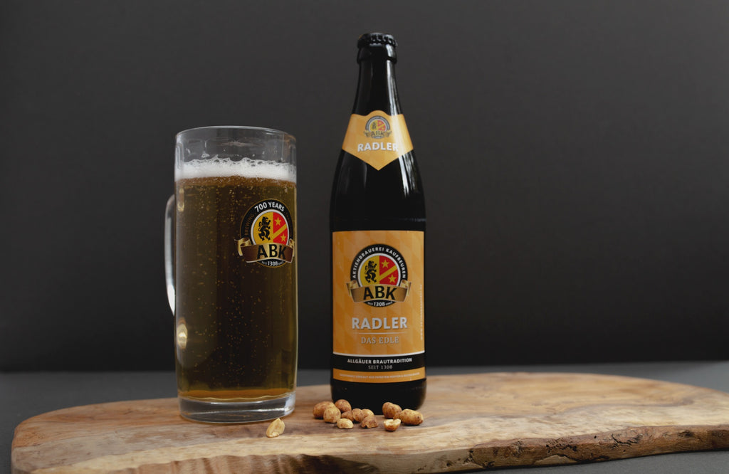 A tankard of ABK radler with a bottle of beer next to it