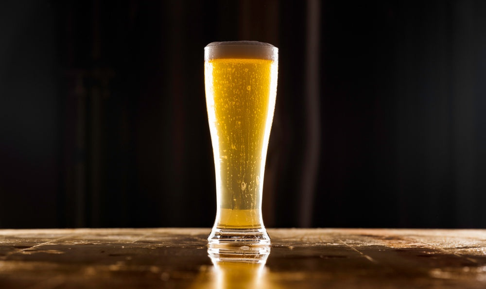 A tall glass of pale colored German pilsner beer