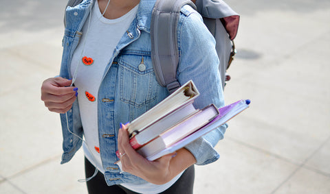 Girl with a backpack and holding books