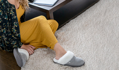 Woman sitting on carpet wearing grey Nuknuuk slippers