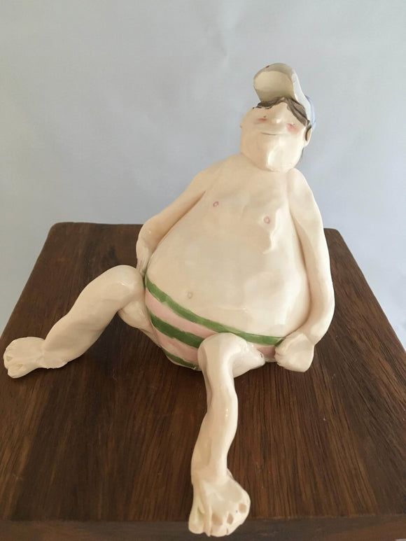 Pottery Beach People, Sitting Man, Large, Brown Hair, Hat, Glasses, Pink-Green Striped Speedo - Two Hoots Gift Gallery