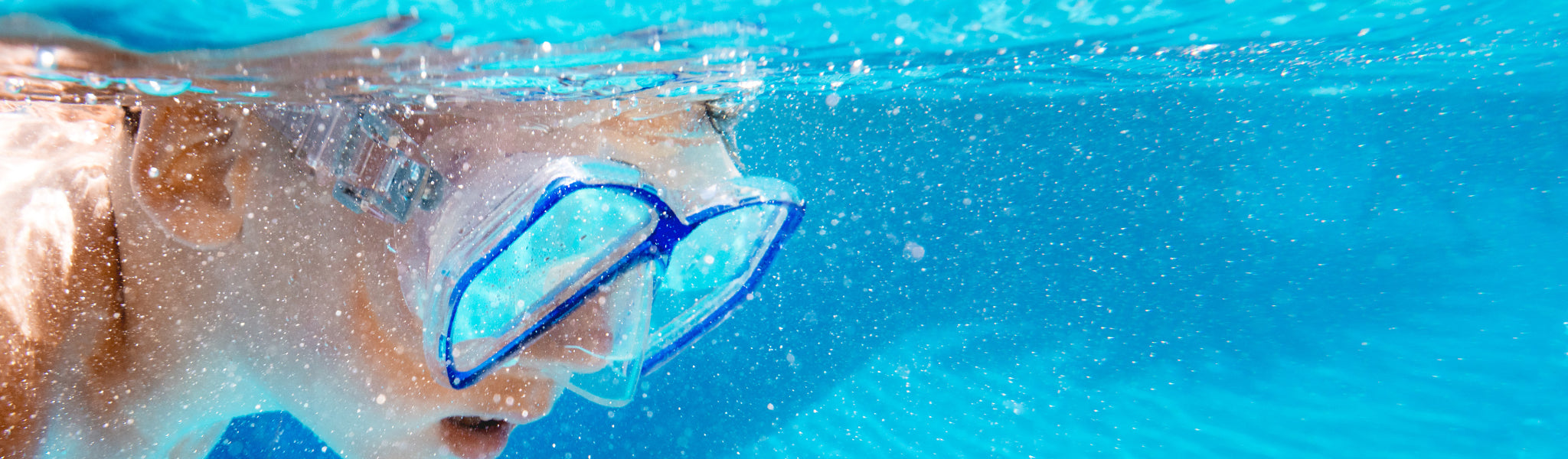 Child swimming in pool with snorkel mask underwater