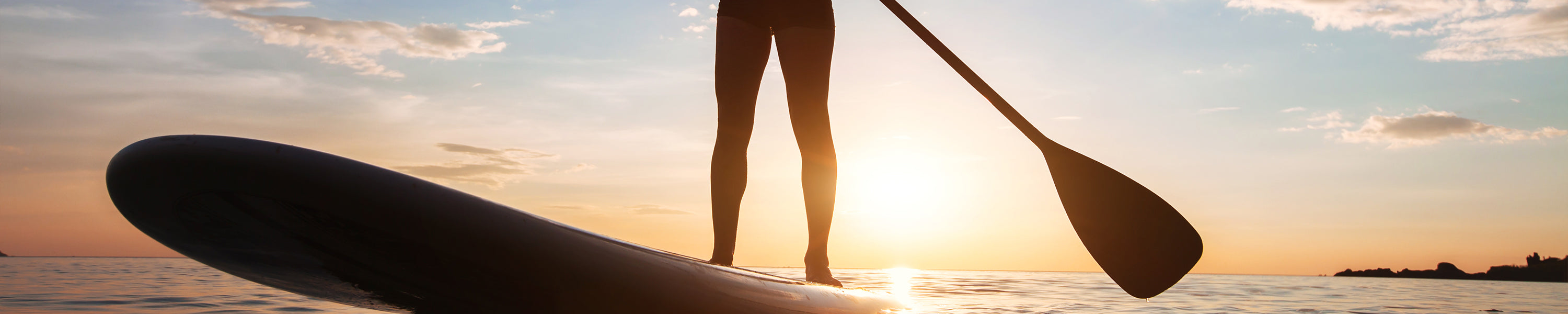 close up of a silhouetted paddle boarder standing on their board