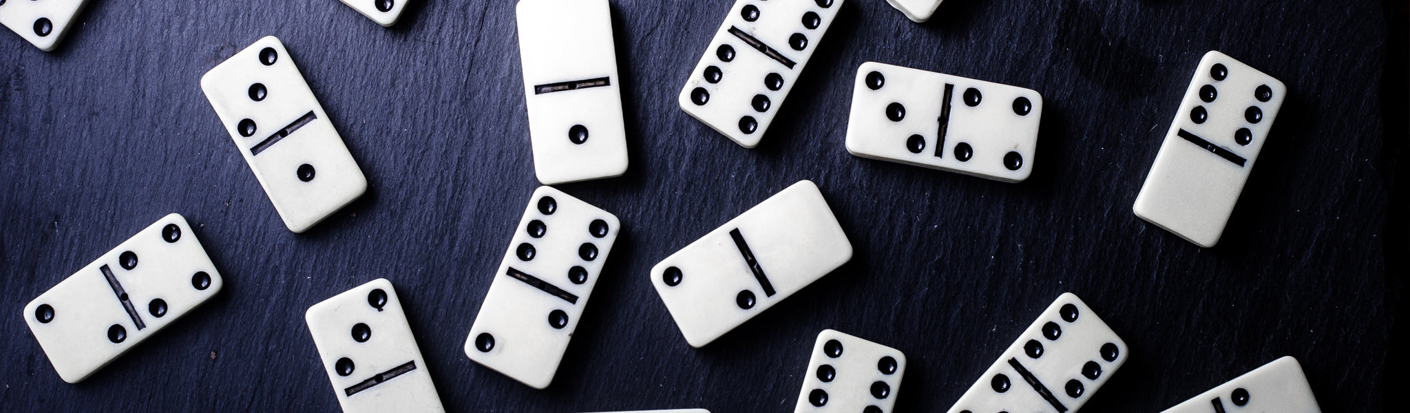 dominoes scattered on a dark wood table