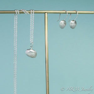side view of ark clam seashell drop earrings in silver with matching ark clam necklace