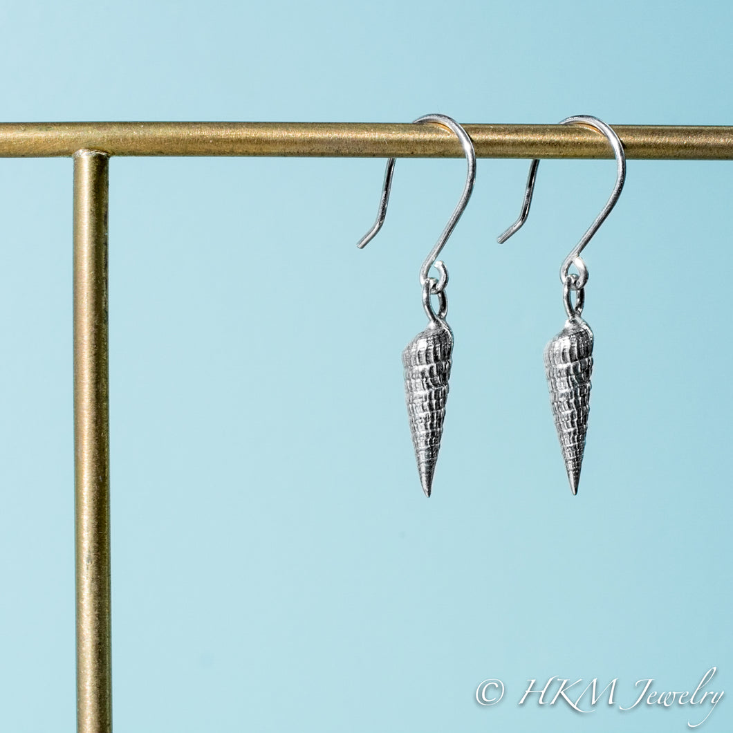 side close up view of auger snail shell dangle earrings in polished silver by hkm jewelry