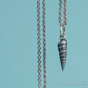 close up front view of the auger snail shell necklace in oxidized silver by hkm jewelry
