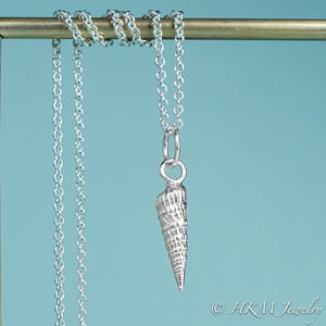 close up front view of the auger snail shell necklace in polished silver by hkm jewelry