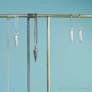 to scale view of auger snail shell dangle earrings and matching necklaces in polished and oxidized silver by hkm jewelry