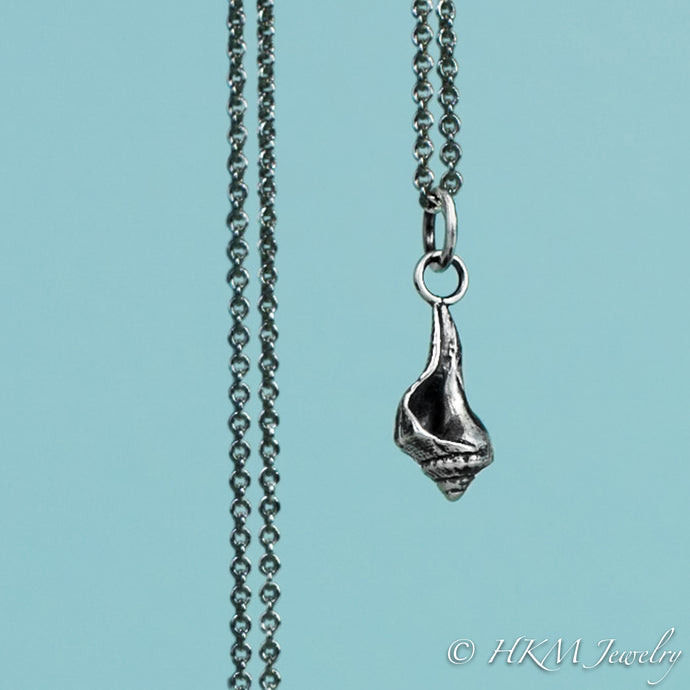 close up front view of baby knobbed whelk necklace in oxidized finish by hkm jewelry