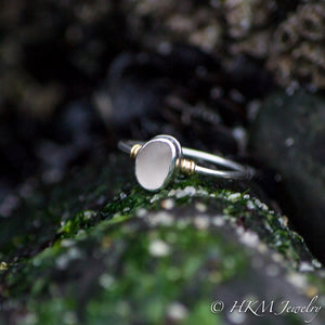 side view of a raw cape may diamond ring with 14k wrapped knot details over silver by hkm jewelry laying in green seaweed