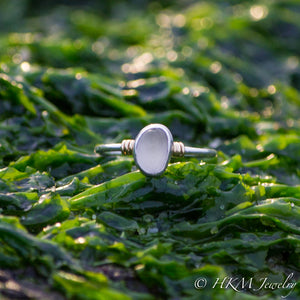 a raw cape may diamond ring with 14k wrapped knot details over silver by hkm jewelry lays in green seaweed