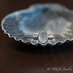 raw cape may diamond ring with knot detail by hkm jewelry laying in scallop shell