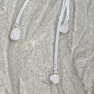 small medium and large raw cape may diamond necklaces in sterling bezels by hkm jewelry laying in sand