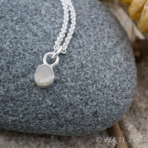close up front view of small size raw cape may diamond necklace in a sterling silver bezel by hkm jewelry