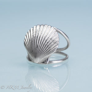 close up angled front view of large scallop shell ring on a double band in sterling silver by hkm jewelry