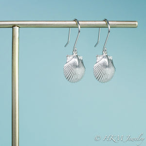 close up side view of the small polished scallop shell dangle earrings in sterling silver by hkm jewelry