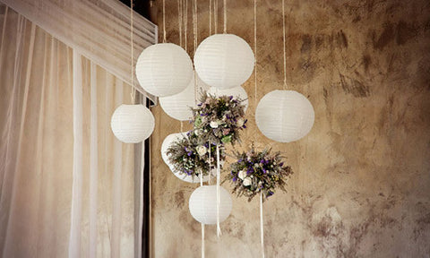 Round white paper lanterns mixed with flowers