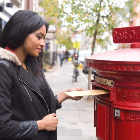 Black woman posting a letter