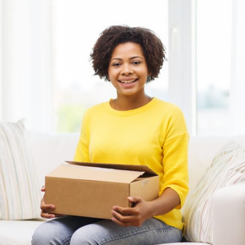 Black woman opening a parcel