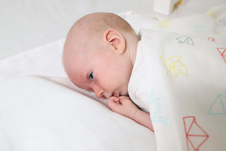 Baby facing down on white sheet, covered in printed musluv as a blanket