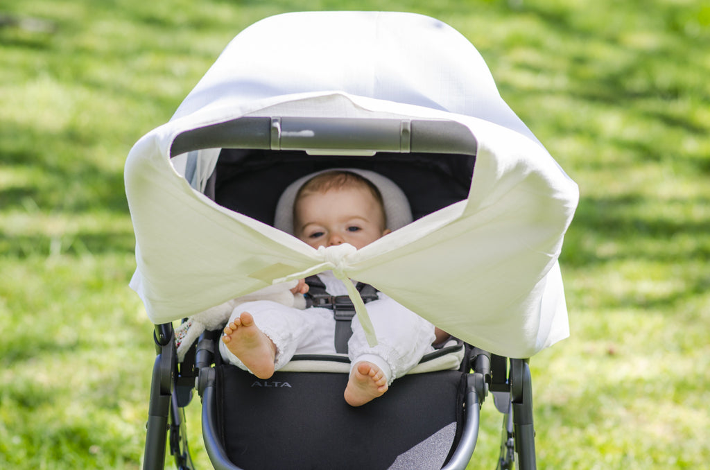 Baby in a pram with musluv baby sun shade cover and ventilation gaps