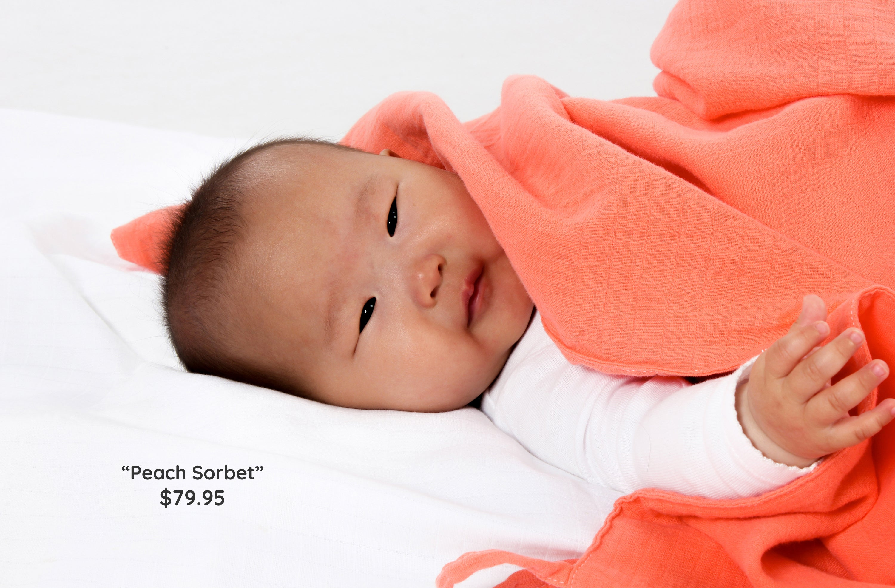 Baby lying on white musluv cover, covered in peach musluv