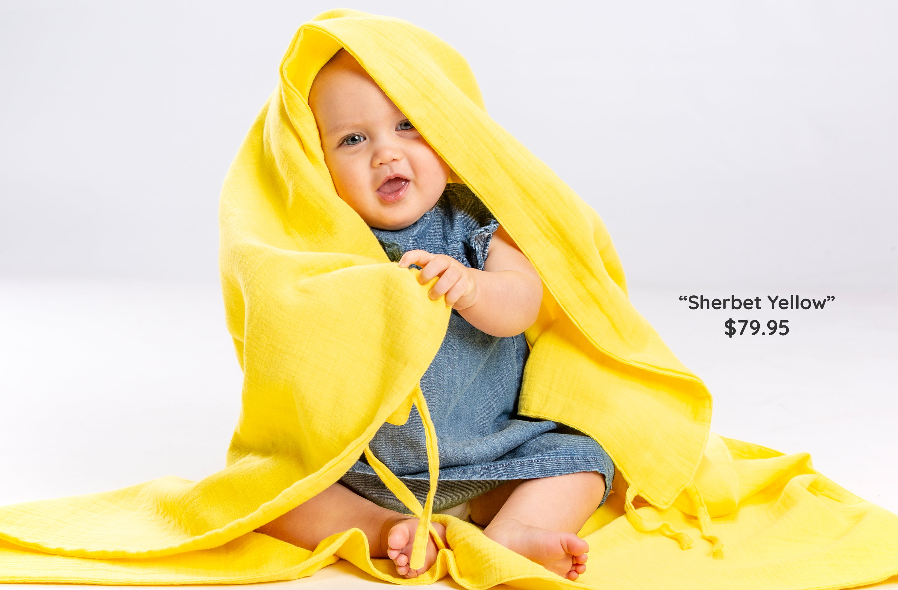 Baby with yellow musluv cover as a hood