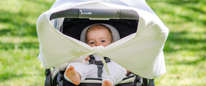 Cute baby peeking under muslin pram sun shade canopy