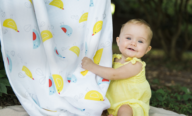 Baby holding musluv baby sun shade cloth smiling