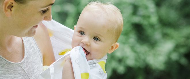 Happy baby chewing on musluv sun protection baby cover