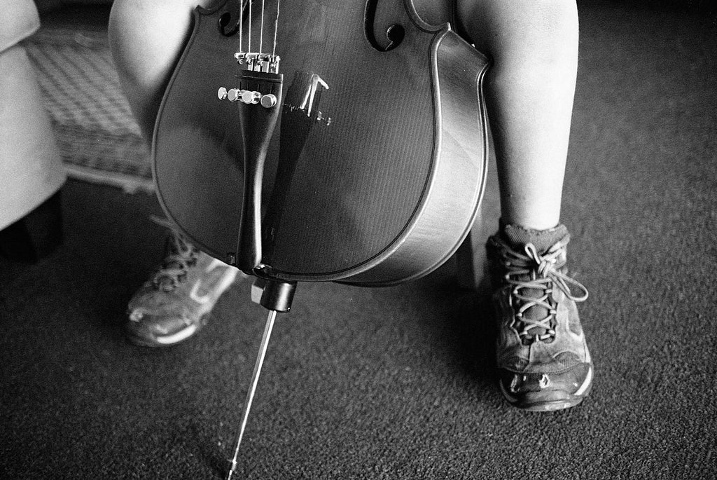 Film photo by Katie Lobodzinski of a child in hiking boots playing a cello