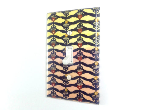 A colorful single toggle switch plate. The background has light yellow which fades to a peachy orange at the bottom and is covered with a dark blue geometric pattern.