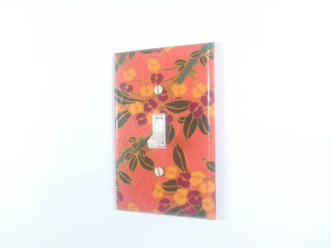 A Peachy Orange Single Toggle Switch Plate with Orangish Yellow and Plum Flowers, Green Leaves and Gold Details by The Orange Chair Studio.