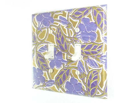 A large bluish purple floral design covers this double toggle swtich plate, with a metallic gold background weaving in and out of the tan leaves and vines.
