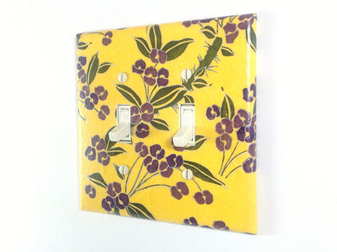 A bright yellow double toggle switch plate with dark and light plum colored flowers, green leaves, and gold details by The Orange Chair Studio.
