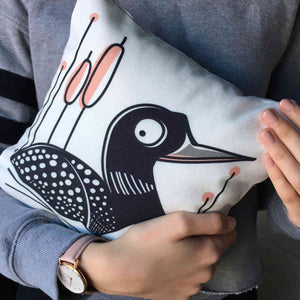 Loon Pillow showing front loon illustration cradled in hands