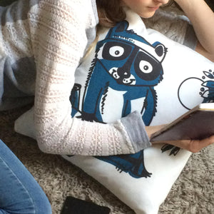 "Girl cuddling with our Raccoon 18"" cotton twill pillow"