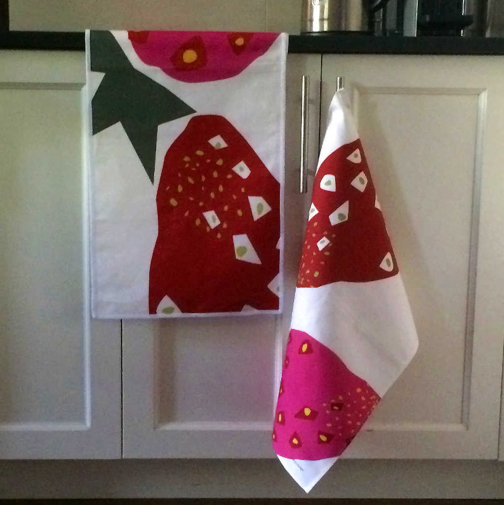 Strawberry table runner and tea towel displayed in kitchen