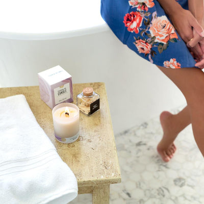 A spa setting with the Lavender Magnolia essential oil candle for relaxation by Edens Garden