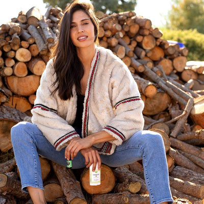 Woman next to chopped wood with Frankincense Lime Natural Essential Oil Deodorant with forest and citrus by Edens Garden